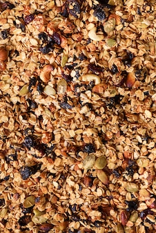 Organic homemade roasted granola with nuts and rasins on baking sheet. food for breakfast. meal background, granola texture