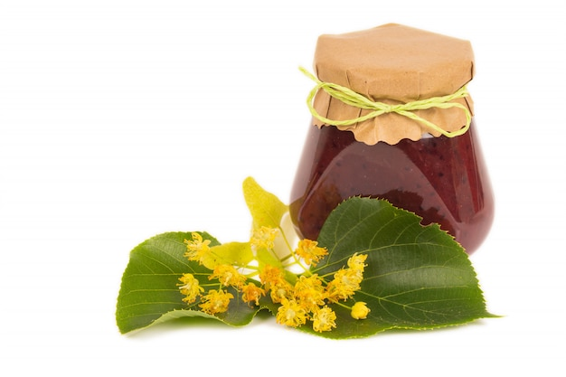 Organic honey in glass jar with linden flowers, isolated