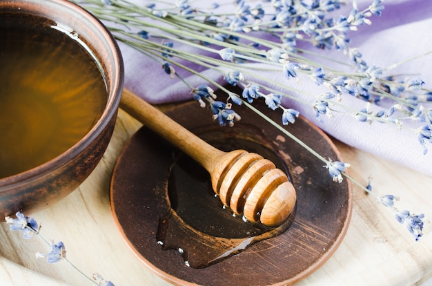Organic honey and lavender flowers on wooden table.