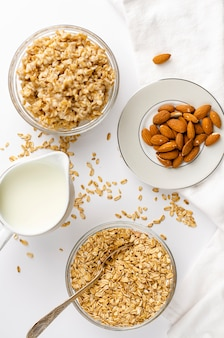 Organic ingredients for healthy breakfast - rolled oats, milk and almonds