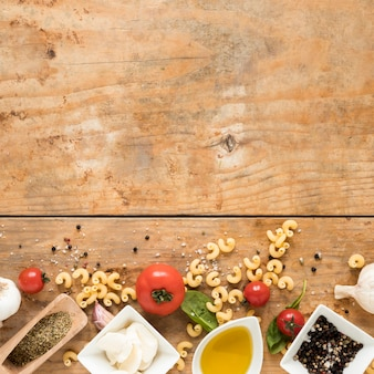 Organic italian ingredients and raw macaroni pasta over wooden table with space for text