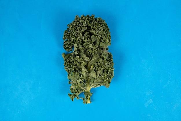青いテーブルの上の有機ケールの葉。上面図。