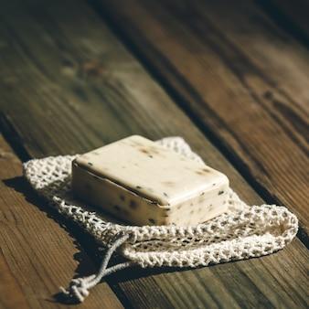 Органическое мыло лаванды на деревянных фоне. эко натуральные аксессуары для ванных комнат, натуральные косметические средства и инструменты. ноль отходов концепции. пластик бесплатный.