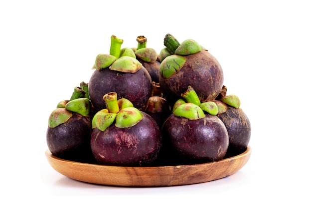 Organic mangosteen in wooden tray on white