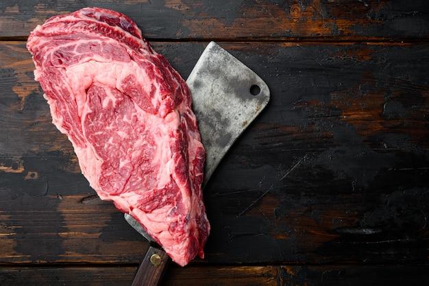 Органическое мясо мраморной говядины набор стейков и приправ, вырез на ребре, старый нож мясника, на фоне старого темного деревянного стола, плоская планировка, вид сверху, с местом для текста