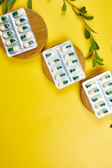 Organic medical pills, capsules in blisters with herbal plant on a yellow surface