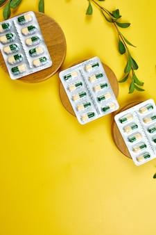 有機薬用錠剤、黄色い表面にハーブ植物が付いた水ぶくれのカプセル