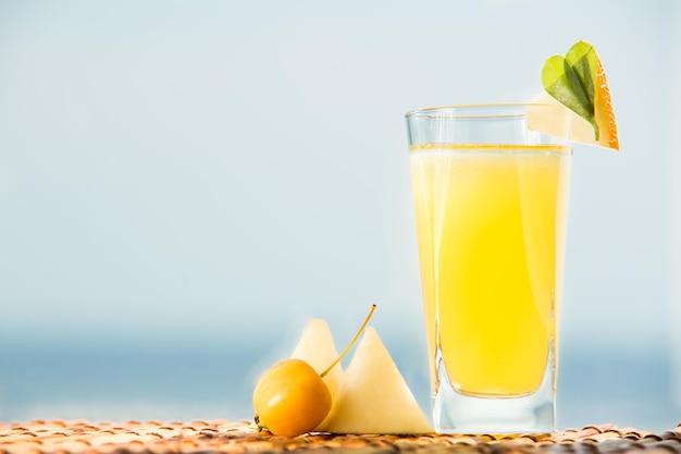 ミネラルウォーター入りのオーガニックメロンレモネード。メロンジュースと氷を背景に海とカクテル。 Premium写真