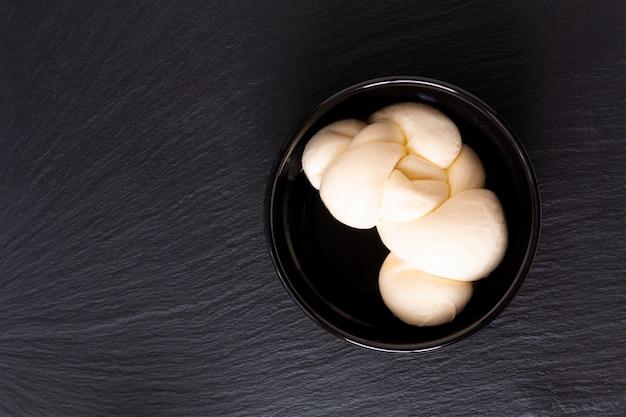 Organic mozzarella cheese in black ceramic cup with copy space