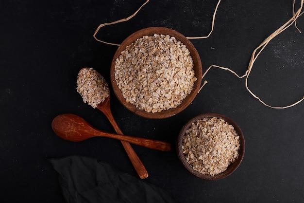 Органические мюсли в деревянных чашках и ложке, вид сверху.