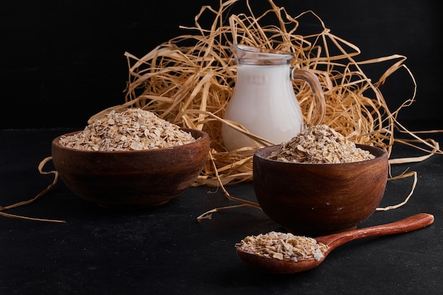 牛乳の瓶と木製のカップとスプーンで有機ミューズリー。