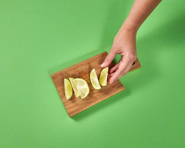 나무 보드에 유기 자연 신선한 라임 조각. 여성의 손은 수제 천연 레모네이드를 준비하기 위해 라임 조각을 취합니다. 건강한 자연 채식 음식의 개념입니다.