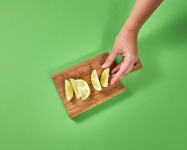 Organic natural fresh lime slices on a wooden board. female hands takes a piece of lime for preparing homemade natural lemonade. concept of healthy natural vegetarian food.