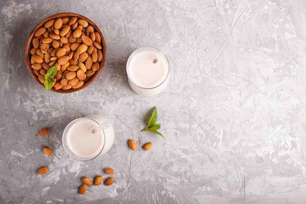 Organic non dairy almond milk in glass and wooden plate with almond nuts on a gray concrete.