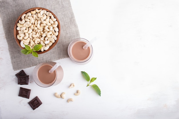 Organic non dairy cashew chocolate milk in glass and wooden plate with cashew nuts on a gray concrete.
