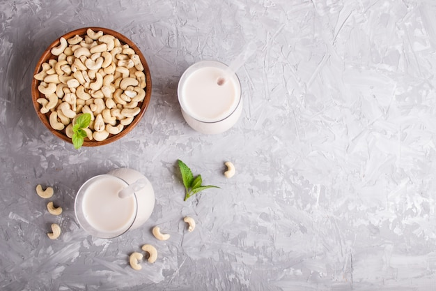 Organic non dairy cashew milk in glass and wooden plate with cashew nuts on a gray concrete.