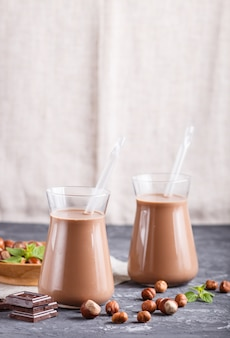 Organic non dairy hazelnut chocolate milk in glass and wooden plate with hazelnuts on a black concrete background.