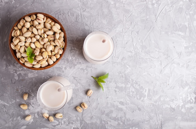 Organic non dairy pistachio milk in glass and wooden plate with pistachionuts on a gray concrete.
