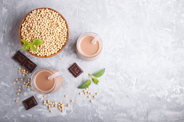Organic non dairy soy chocolate milk in glass and wooden plate with soybeans on a gray concrete.
