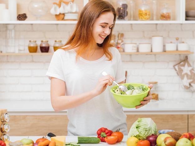 유기농 영양. 보건 의료. 여성의 식습관. 신선한 그린 샐러드 그릇으로 젊은 여자를 웃 고.