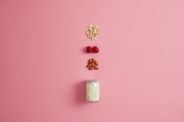 有機栄養、健康的な朝食のコンセプト。おいしいスナックを作るための瓶に入ったヨーグルトまたはビーガンミルク、オートミールシリアル、ラズベリー、アーモンドナッツ。天然成分。ベジタリアンの食事とダイエット