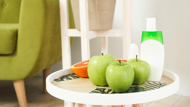 天然木のテーブルの上の有機オレンジと緑のリンゴ