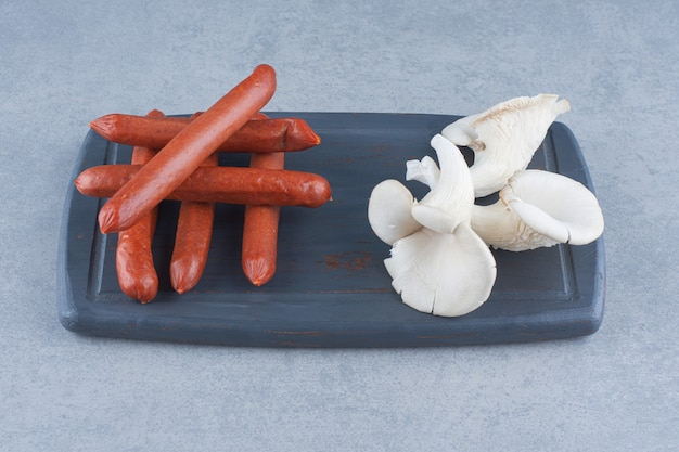 Organic oyster mushroom and salami on wooden board.