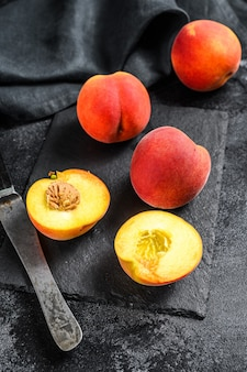 Organic peaches fruit on a black stone board. black background. top view.