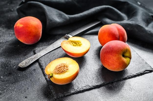 黒い石のボード上の有機桃の果実
