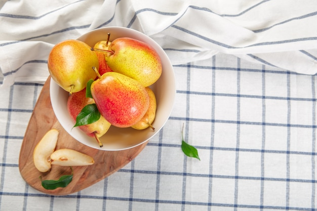 Organic pears laying down on a lightly dotted kitchen cloth