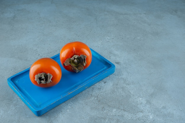 Органическая хурма на голубой деревянной тарелке, на мраморном фоне. фото высокого качества
