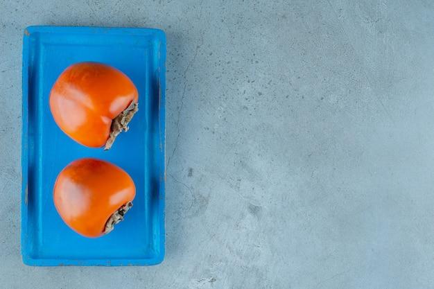 Органическая хурма на голубой деревянной тарелке, на мраморном фоне.