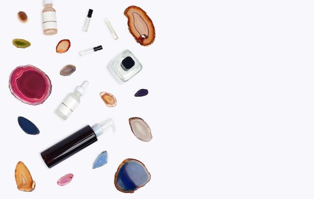 Органическая косметика аптеки с натуральным камнем агата на белом фоне. плоская планировка. вид сверху бутылок сливок. натуральные косметические товары. концепция чистой красоты.