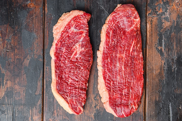 Organic picanha beef meat steaks, over dark old wooden background,  top view space for text.