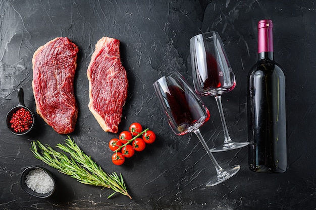 Organic picanha steaks near bottle and glass of red wine, over black textured table top view.