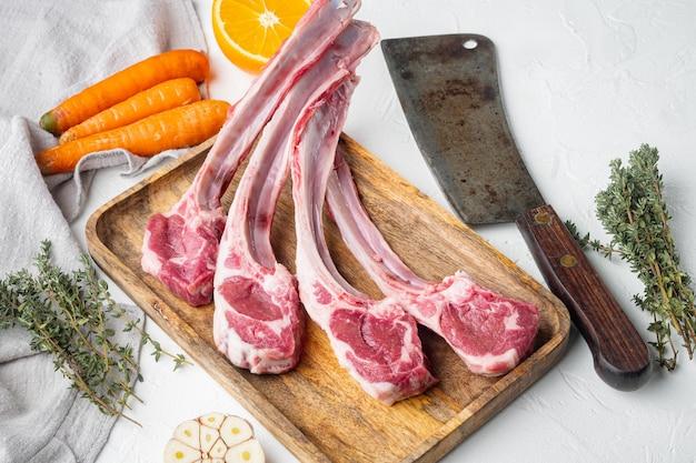 Органические куски баранины, каре ягненка, сырое с костями, с ингредиентами: морковь, апельсин, зелень и старый нож мясника, на белом каменном столе