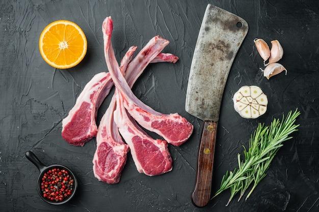 Органические куски баранины, каре ягненка, сырое с костями, с ингредиентами, морковный апельсин, зелень, на черном каменном столе, плоский вид сверху