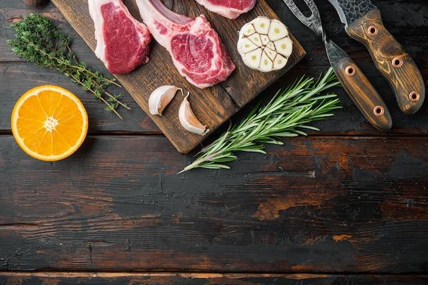 Органические куски баранины, каре ягненка, сырое с косточкой, с ингредиентами, морковный апельсин, зелень, на старом темном деревянном столе, плоская планировка, вид сверху