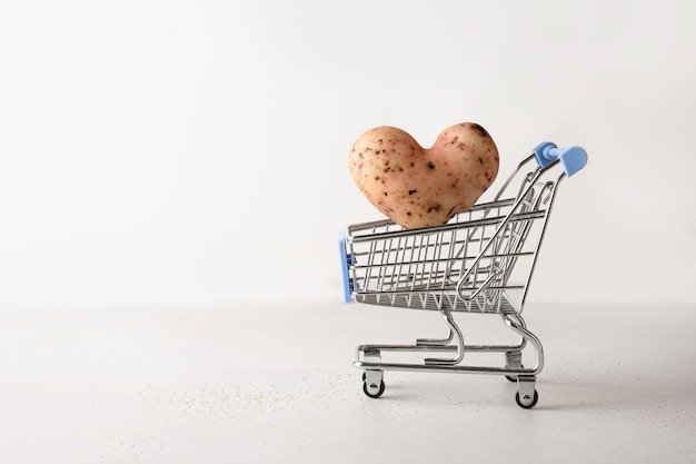 Organic potato in shape of heart flying into grocery cart on white background. concept love homegrown ugly vegetables.