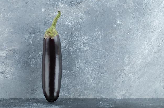 Melanzane viola organiche su fondo grigio.
