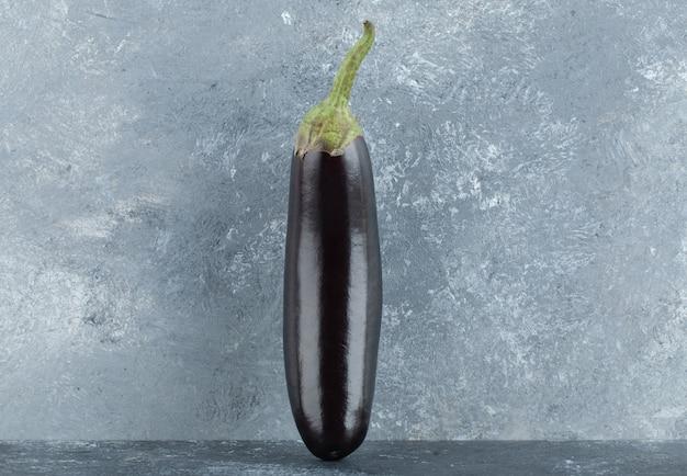 Organic purple eggplants on grey background.
