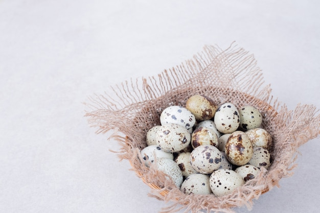 Organic quail eggs in bowl on white surface.