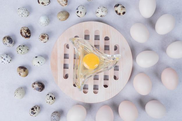 Uova di quaglia biologiche e uova di gallina su superficie bianca con tuorlo d'uovo.