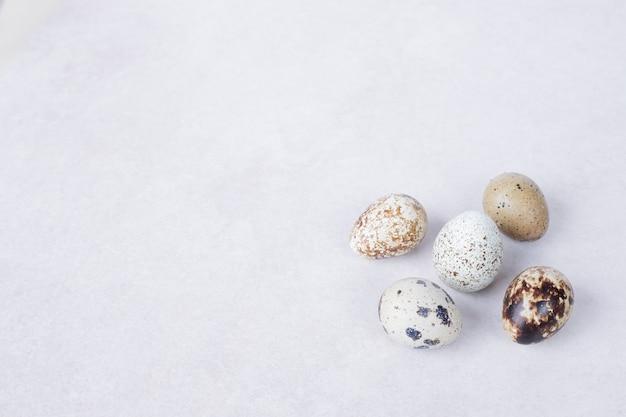Органические яйца триперсток на белой поверхности.