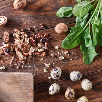 テキスト用のスペースがある木製のテーブルに有機ウズラの卵、クルミ、ほうれん草。ダイエットサラダ用の商品一式。フラットレイ