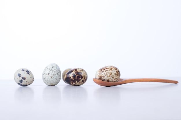 Uova di quaglia organiche sulla superficie bianca con il cucchiaio.