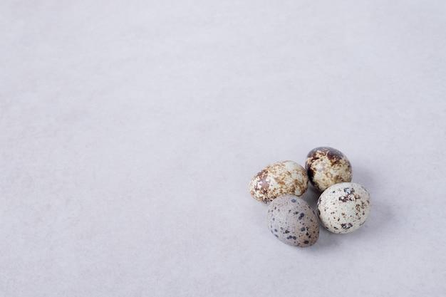 Uova di quaglia organiche sulla superficie bianca.