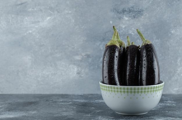 Organic raw eggplants in bowl on grey background.
