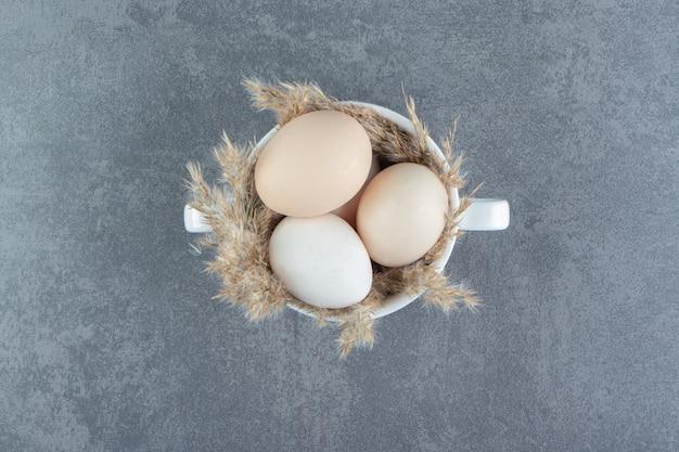 Uova crude organiche in tazza bianca.