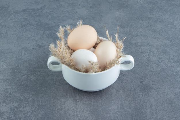 Uova crude biologiche in tazza bianca